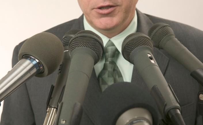 Man Speaking Into Microphones